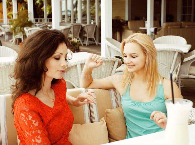 Retrato de dos amigas bastante modernas en la consumici?n interior del aire abierto del caf? y hablar, teniendo charla y coctail fotos de archivo