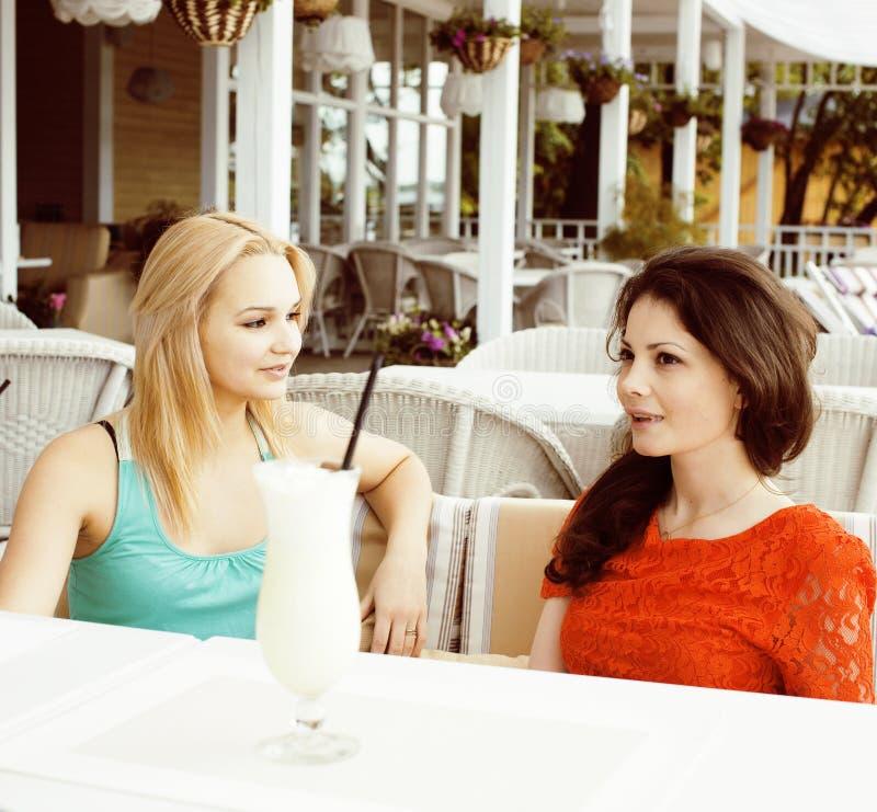 Retrato de dos amigas bastante modernas en la consumici?n interior del aire abierto del caf? y hablar, teniendo charla y coctail fotos de archivo libres de regalías