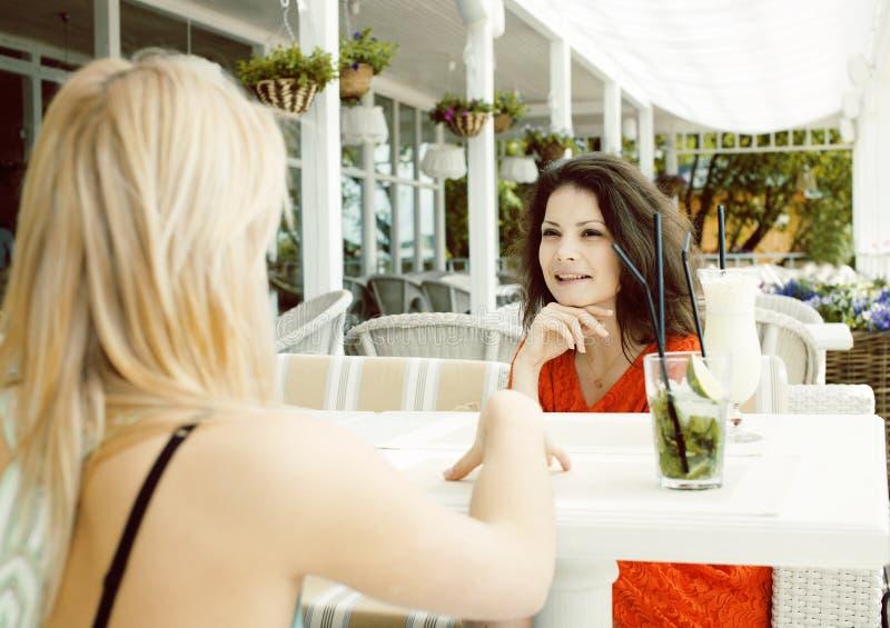Retrato de dos amigas bastante modernas en la consumici?n interior del aire abierto del caf? y hablar, teniendo charla y coctail fotografía de archivo libre de regalías