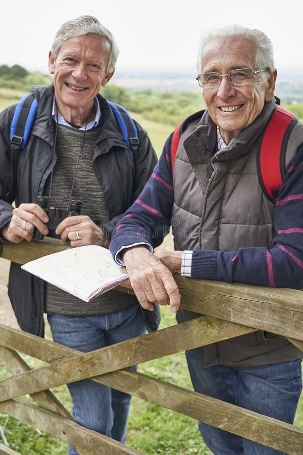 Retrato De Dos Amigos Varones Retirados En Vacaciones A Pie Descansando En La Puerta Con Mapa fotos de archivo libres de regalías
