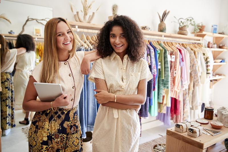 Retrato de dos ayudantes femeninos de las ventas con el funcionamiento de la tableta de Digitaces en tienda de la ropa y de regal fotos de archivo
