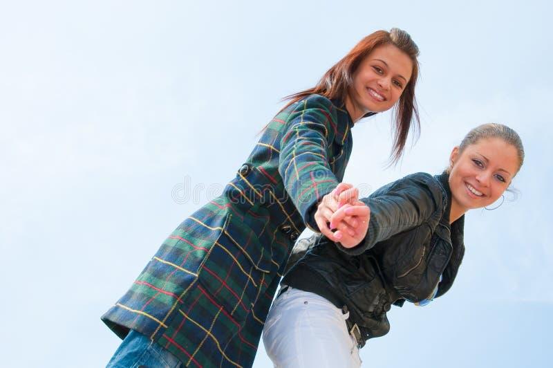 Retrato de dos chicas jóvenes sobre el cielo imagen de archivo