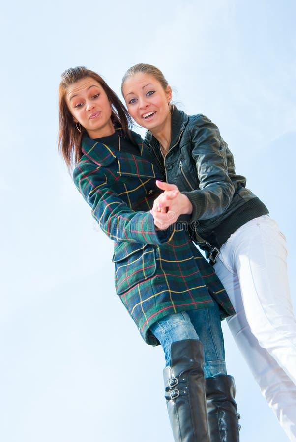 Retrato de dos chicas jóvenes sobre el cielo imagen de archivo libre de regalías