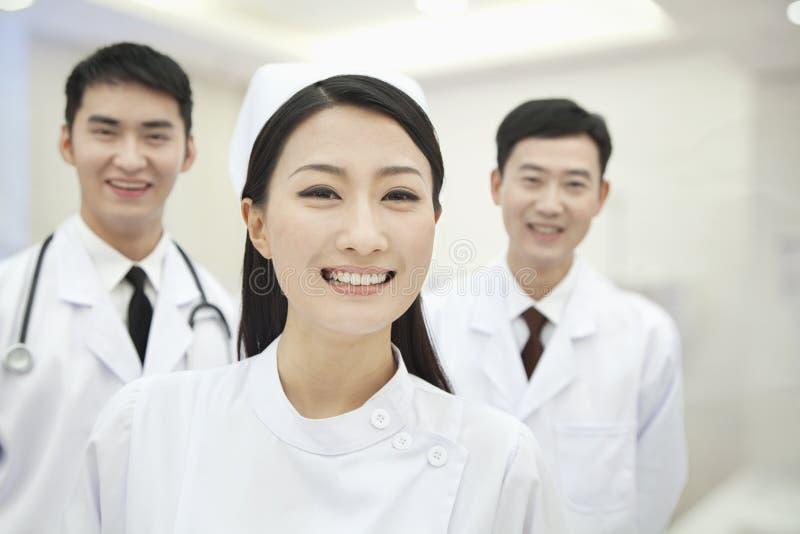 Retrato de dos doctores y de la enfermera, sonriendo y feliz, China foto de archivo libre de regalías