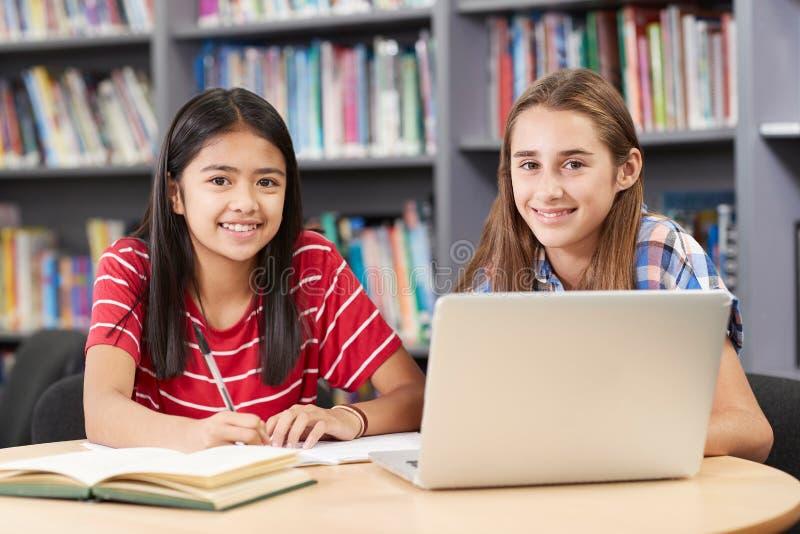 Retrato de dos estudiantes femeninos de la High School secundaria que trabajan en el ordenador portátil adentro fotografía de archivo libre de regalías