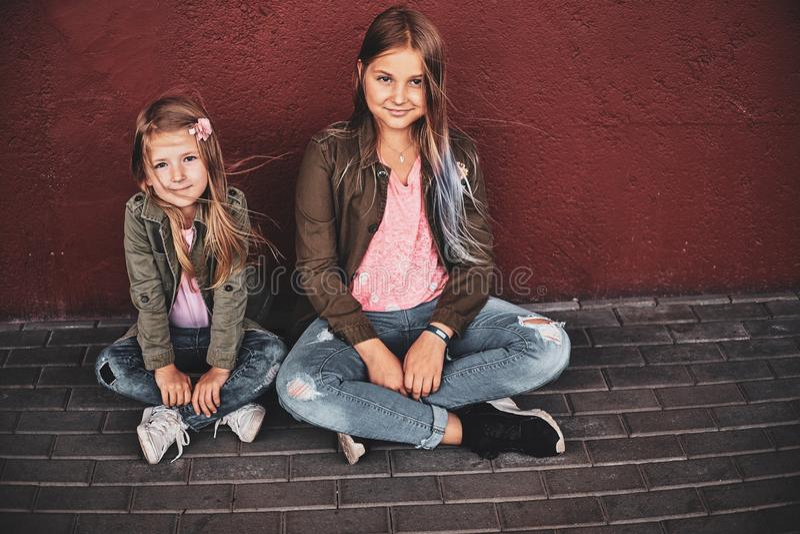 Retrato de dos hermanas bonitas con el monopatín imagen de archivo libre de regalías