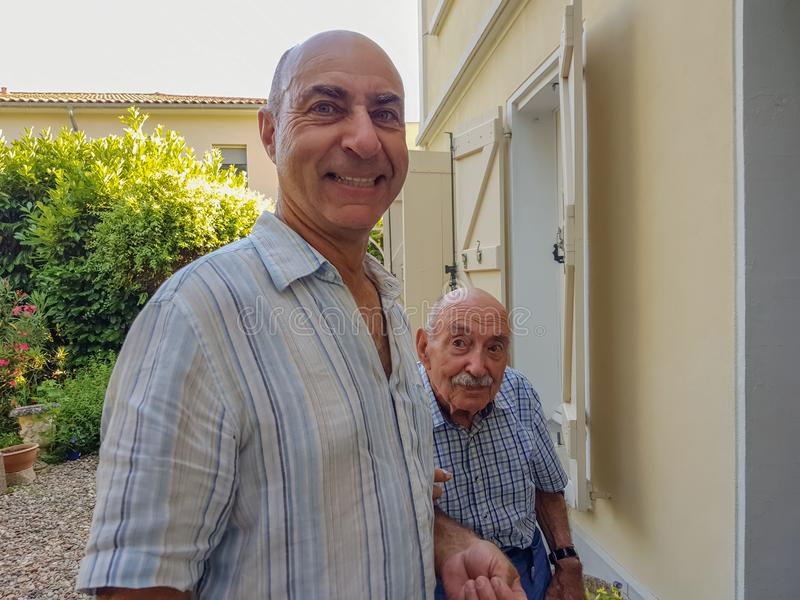 Retrato de dos hombres El hijo mayor apoya a su viejo padre y ayuda el suyo imágenes de archivo libres de regalías