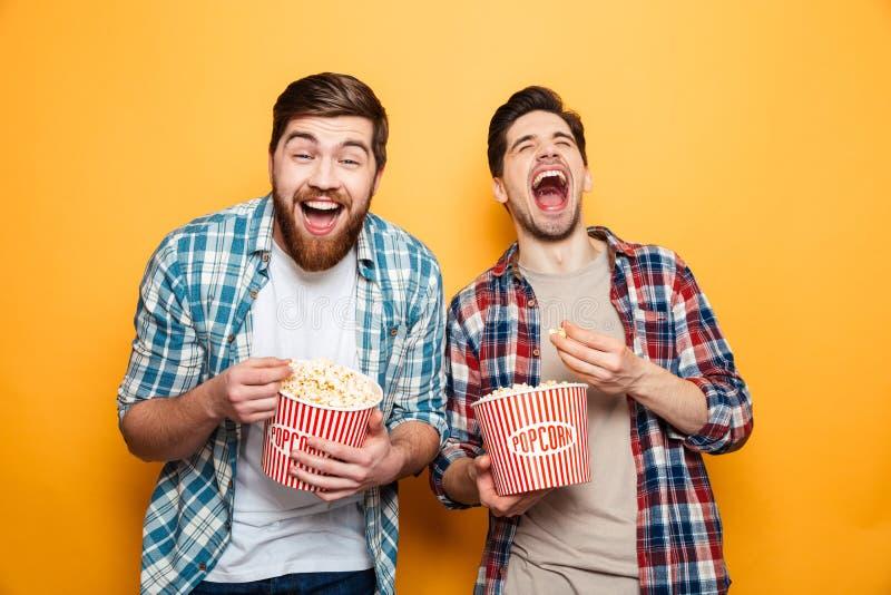 Retrato de dos hombres jovenes alegres que comen las palomitas foto de archivo