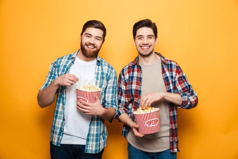 Retrato de dos hombres jovenes alegres que comen las palomitas fotografía de archivo libre de regalías