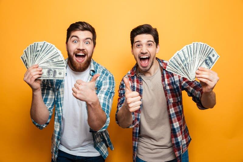 Retrato de dos hombres jovenes alegres que muestran el dinero imágenes de archivo libres de regalías
