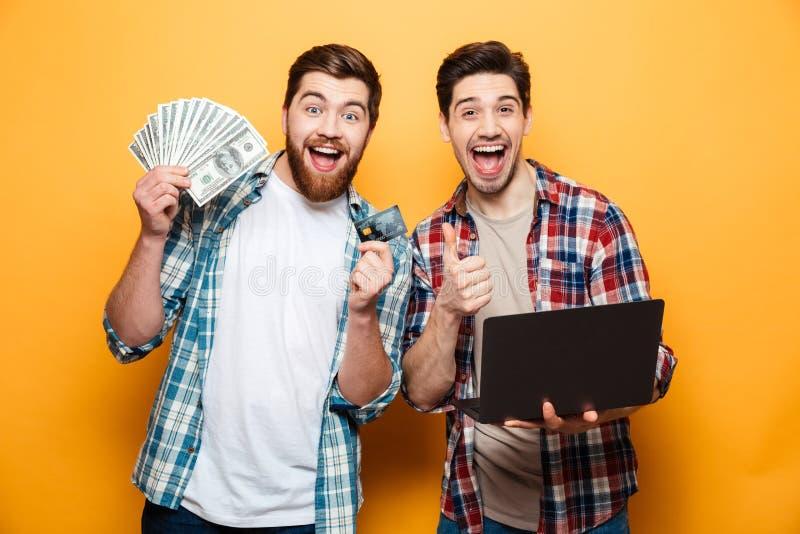 Retrato de dos hombres jovenes alegres que sostienen el ordenador portátil imágenes de archivo libres de regalías