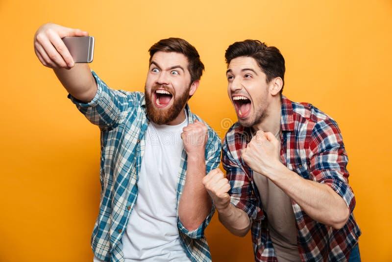 Retrato de dos hombres jovenes alegres que toman un selfie fotografía de archivo libre de regalías