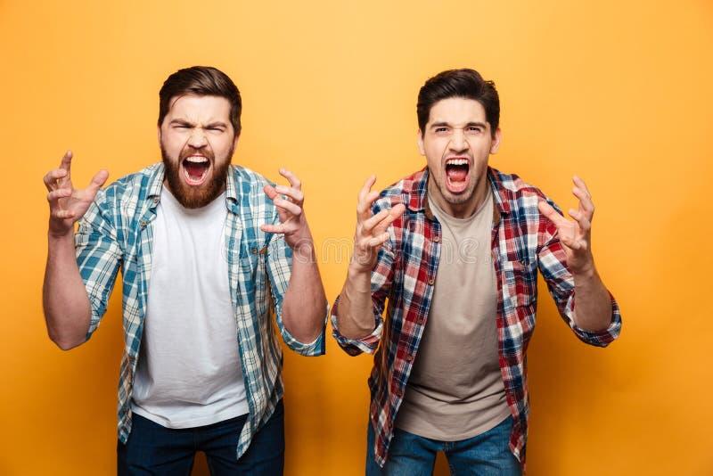 Retrato de dos hombres jovenes enojados que gritan ruidosamente imagenes de archivo