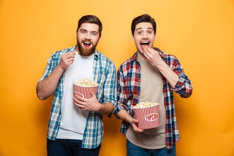 Retrato de dos hombres jovenes felices que comen las palomitas foto de archivo