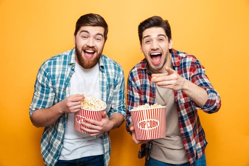 Retrato de dos hombres jovenes felices que comen las palomitas imagen de archivo libre de regalías
