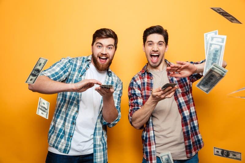 Retrato de dos hombres jovenes felices que dispersan el dinero foto de archivo