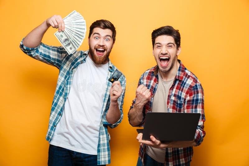 Retrato de dos hombres jovenes felices que sostienen el ordenador portátil fotografía de archivo