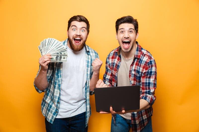 Retrato de dos hombres jovenes felices que sostienen el ordenador portátil fotos de archivo libres de regalías