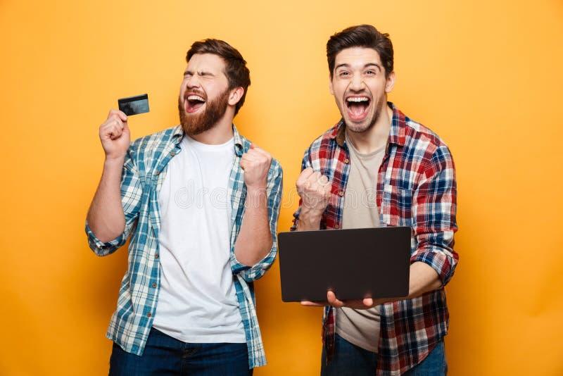 Retrato de dos hombres jovenes felices que sostienen el ordenador portátil foto de archivo libre de regalías