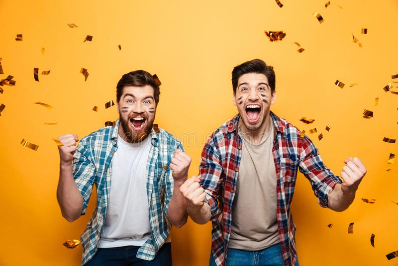 Retrato de dos hombres jovenes felices que sostienen la bola de rugbi fotos de archivo