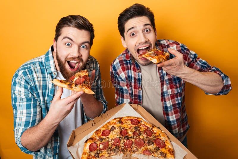 Retrato de dos hombres jovenes hambrientos que comen la pizza foto de archivo