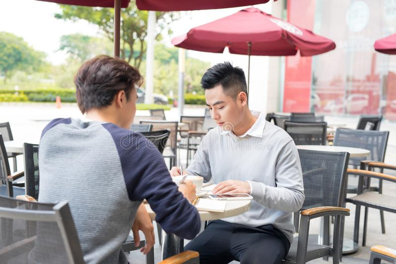 Retrato de dos hombres de negocios asiáticos que se encuentran en una cafetería imagenes de archivo
