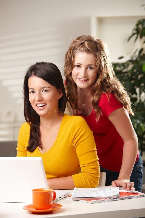 Retrato de dos muchachas con la computadora portátil imagen de archivo libre de regalías