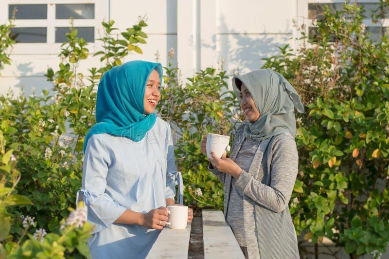 Retrato de dos mujeres del hijab que beben t? delante de la casa y de hablar imagen de archivo