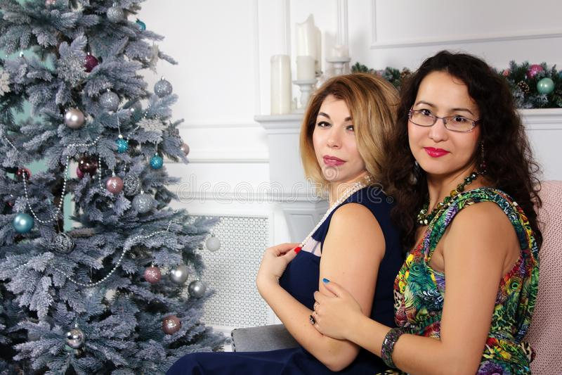 Retrato de dos mujeres hermosas en los vestidos elegantes que abrazan y que miran la cámara sobre fondo brillante del árbol de na imágenes de archivo libres de regalías