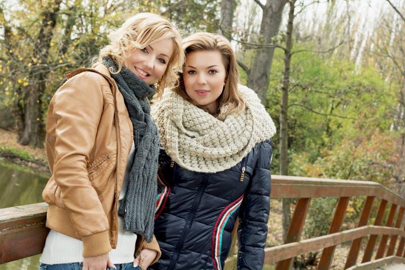 Retrato de dos mujeres hermosas en parque del otoño fotos de archivo