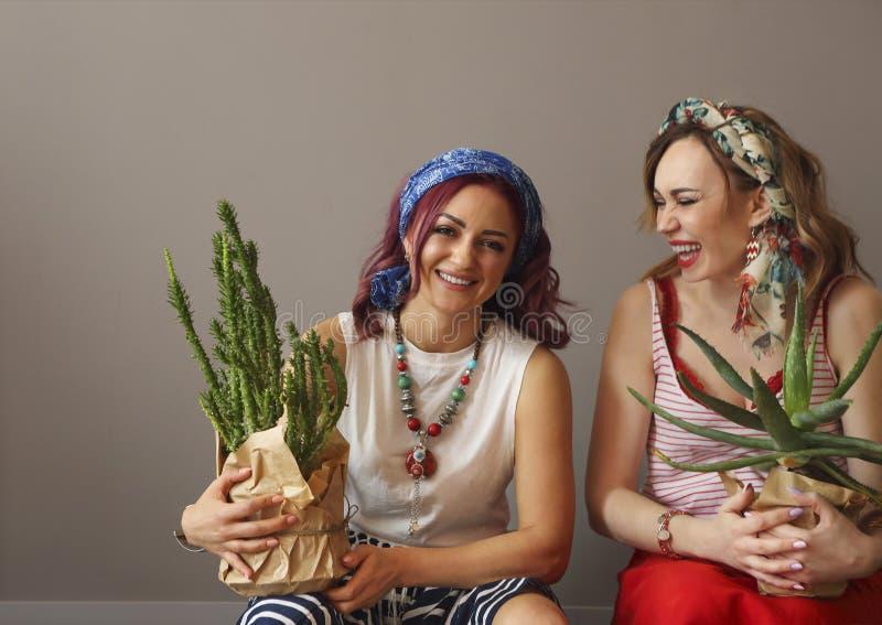 Retrato de dos mujeres hermosas en ropa brillante y del arco en cabeza con los labios brillantes que sostienen los cactus imagenes de archivo