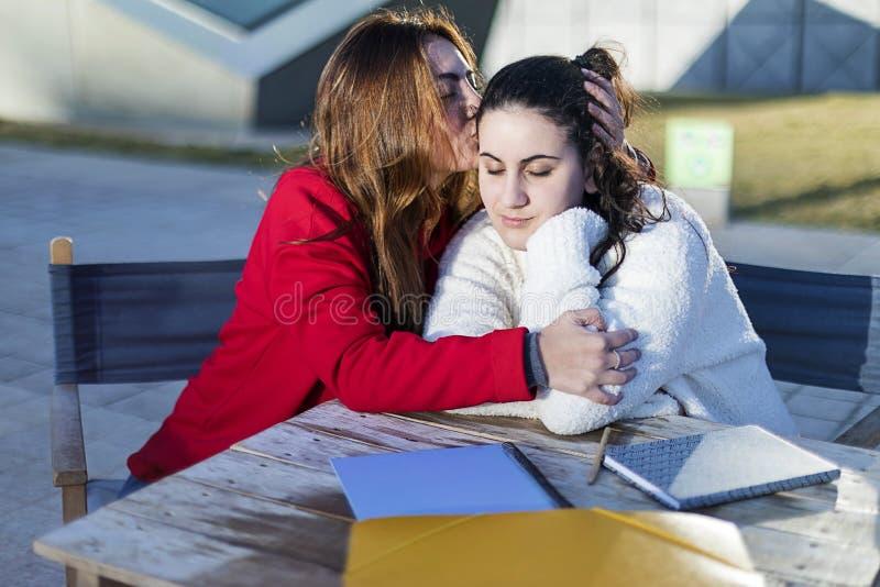 Retrato de dos mujeres jovenes en un café al aire libre mientras que abraza imagen de archivo