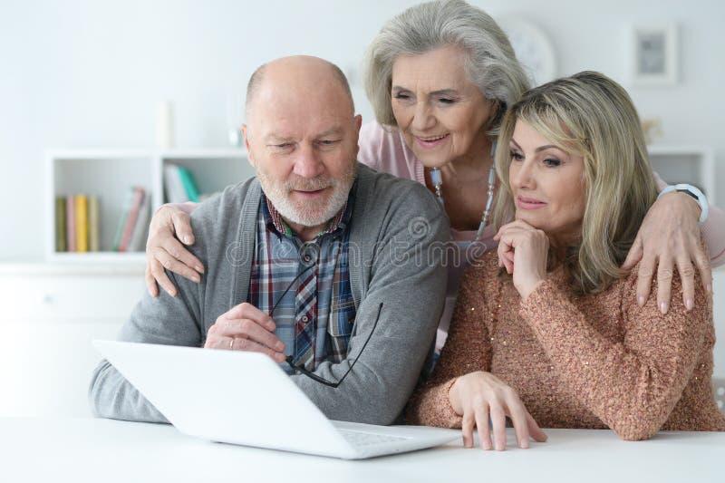 Retrato de dos mujeres mayores y del hombre usando el ordenador port?til fotografía de archivo libre de regalías