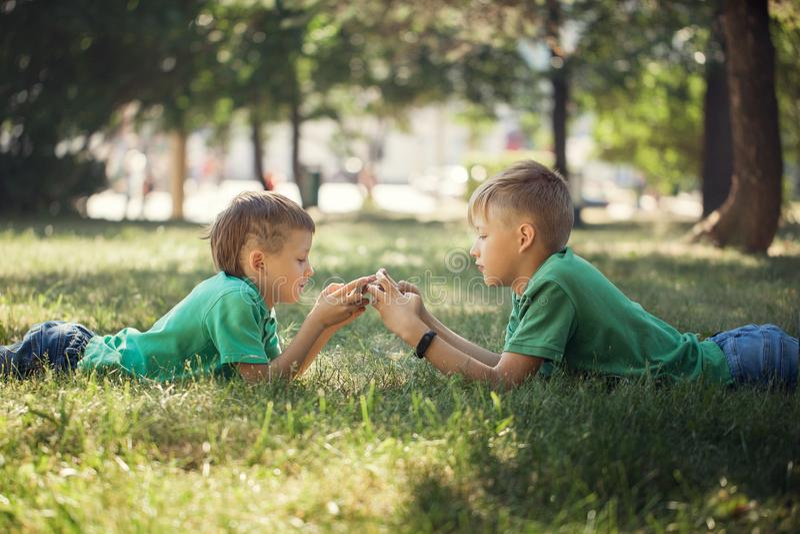 Retrato de dos niños que mienten en hierba verde y que juegan en teléfono móvil fotos de archivo