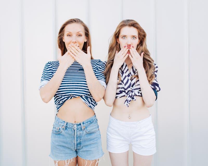 Retrato de dos novias de moda hermosas en los pantalones cortos del dril de algodón y la camiseta rayada que plantean el nex a la fotos de archivo libres de regalías