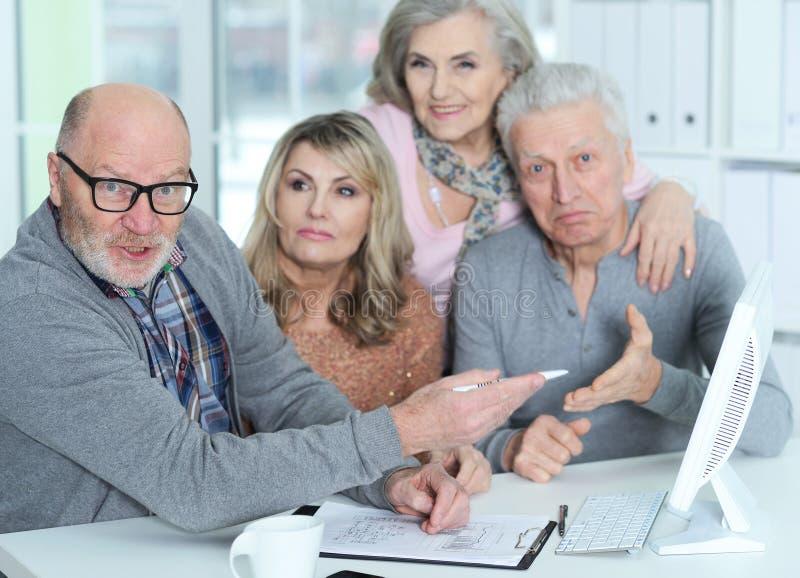 Retrato de dos pares mayores que se sientan en la tabla y que trabajan con el ordenador imagen de archivo
