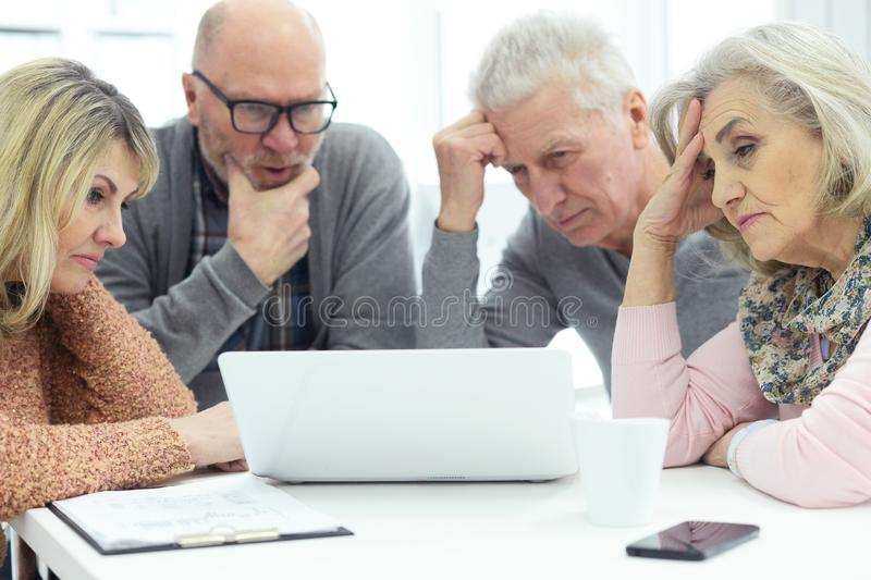 Retrato de dos pares mayores que se sientan en la tabla y que trabajan con el ordenador port?til foto de archivo libre de regalías