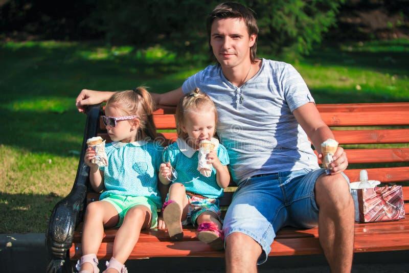 Retrato de dos pequeñas muchachas lindas y del padre joven que comen el helado al aire libre imagen de archivo