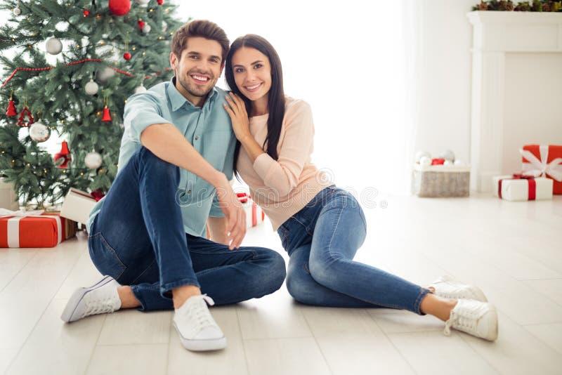 Retrato de dos personas encantadoras parejas sentadas en el suelo disfrutan de Navidad y fiestas navideñas usando vaqueros de den imágenes de archivo libres de regalías