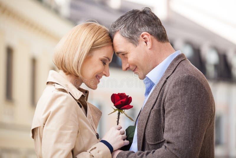 Retrato de dos personas que celebran la rosa y la sonrisa imagen de archivo