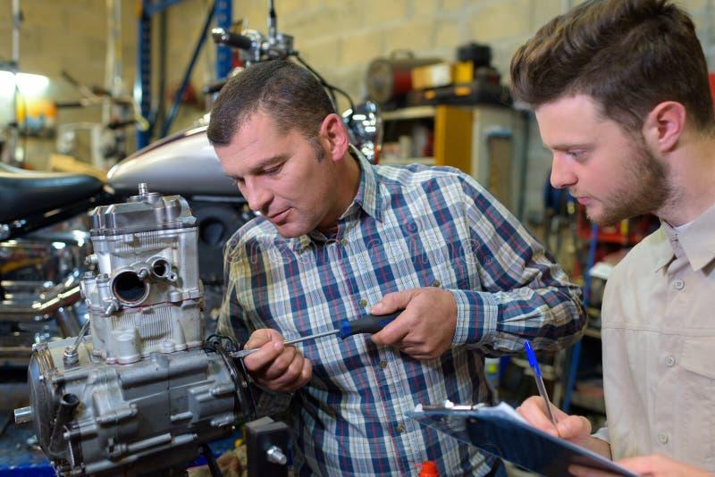 Retrato de dos trabajadores de fábricas que utilizan equipos modernos imagen de archivo