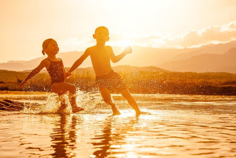 Retrato de duas crianças envelhecidas 3 e 6 que jogam no mar e na água de pulverização em torno deles imagens de stock