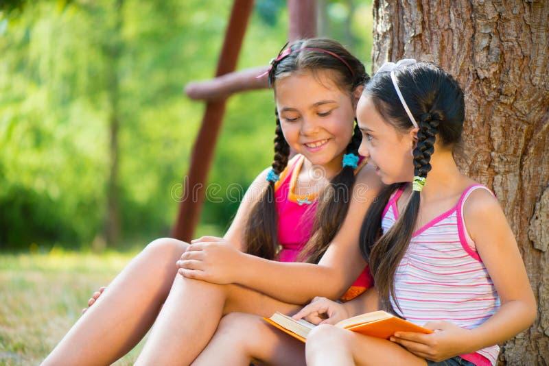 Retrato de duas irmãs felizes que leem no parque imagem de stock