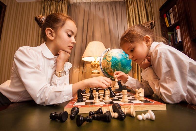 Retrato de duas irmãs mais nova que jogam a xadrez imagens de stock royalty free