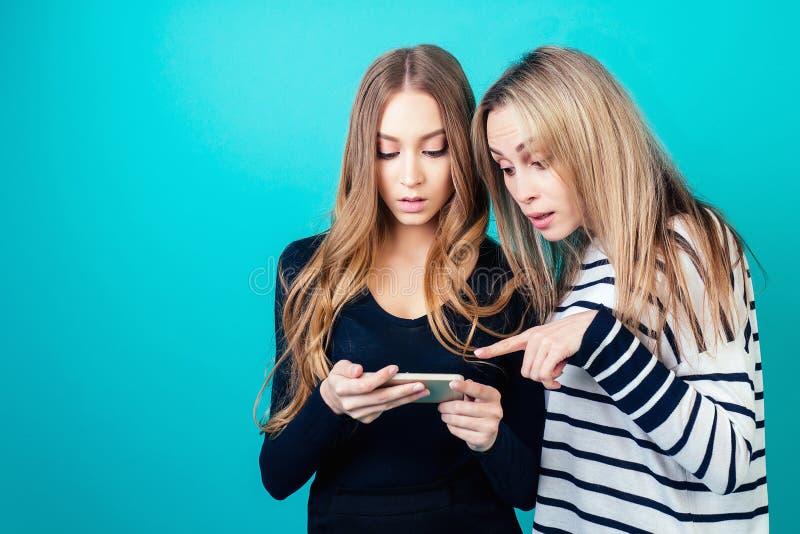 Retrato de duas jovens amigas felizes mulheres com mensagens de maquiagem são reescritas por telefone no estúdio em um imagens de stock