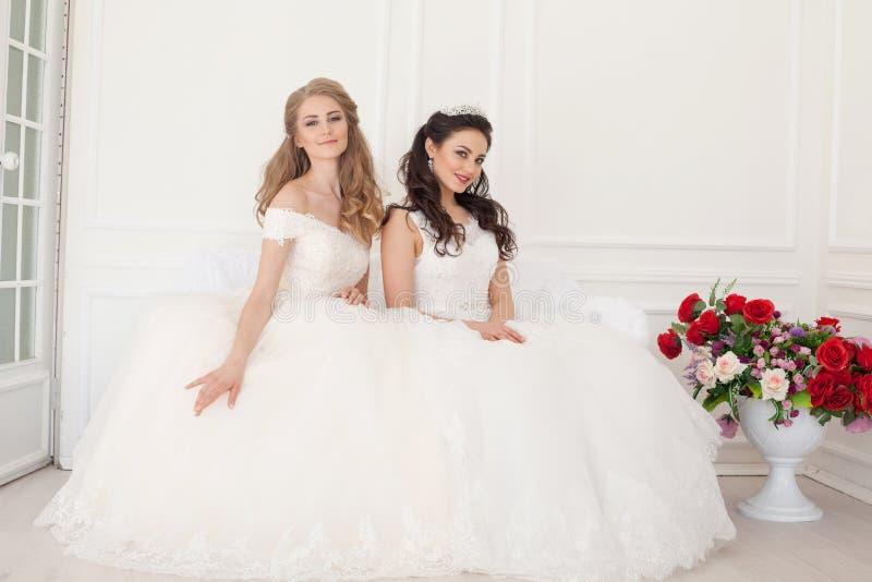 Retrato de duas jovens mulheres em vestidos de casamento em Salão branco imagem de stock