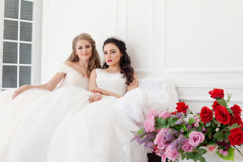 Retrato de duas jovens mulheres em vestidos de casamento em Salão branco imagem de stock royalty free