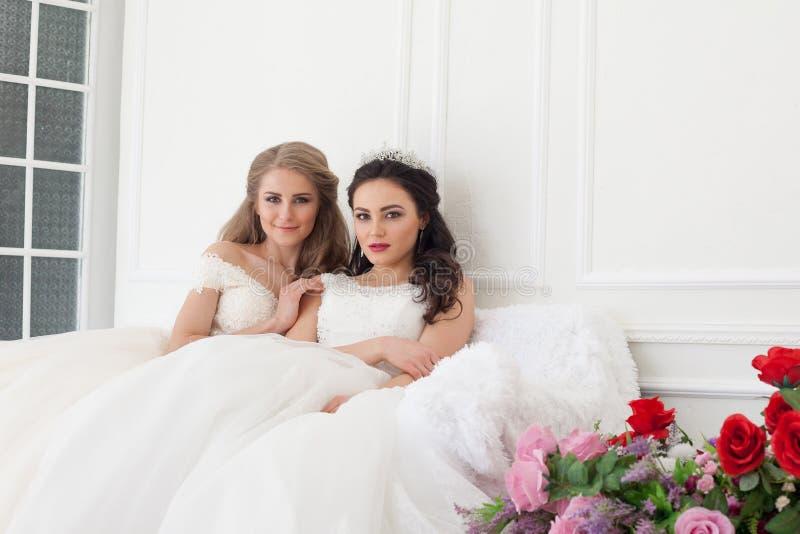 Retrato de duas jovens mulheres em vestidos de casamento em Salão branco imagens de stock royalty free