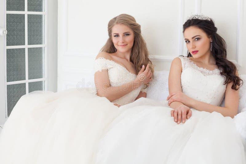 Retrato de duas jovens mulheres em vestidos de casamento em Salão branco fotos de stock royalty free