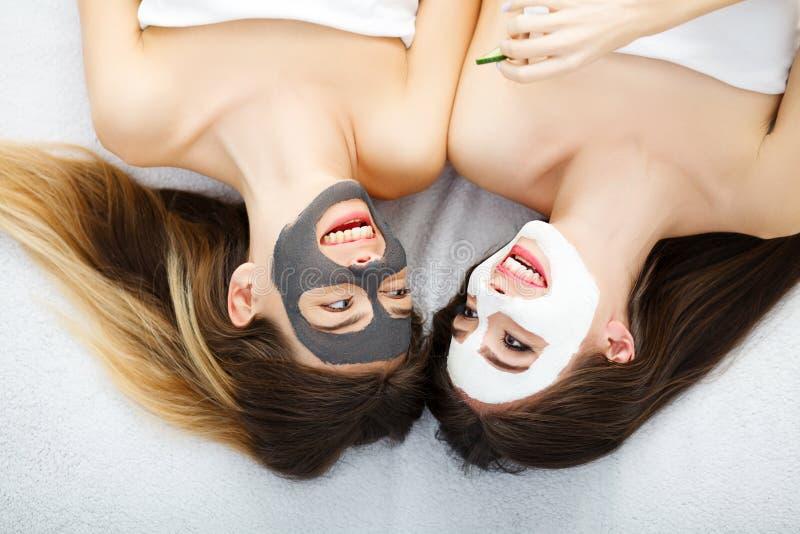 Retrato de duas meninas bonitas com creme facial em suas caras imagem de stock